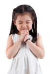 Little girl wishing on white background